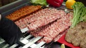borjúhús : Cook hands in black gloves put on fresh raw minced meat with ingredients for cooking decorated lettuce leaves