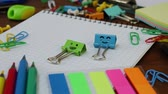 clipe de papel : Smiles Binder Clips on Notebook and School Office Supplies on brown wooden table. Concept of back to school or education in the fall in September or October