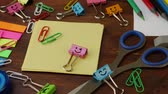 точилка : School stationery on brown wooden table: colored pencils, scissors and paper clips, ruler and pencil sharpener, yellow paper and smiles binder clips. Concept of education or knowledge, back to school
