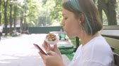 buda : Charming woman in white T-shirt reads message on red smartphone and eating piece of cake with summer park background. Break time concept