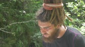 orientamento : Traveler looking for map in forest. Hipster male with dreadlocks examines paper map while traveling near mountain stream