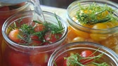 enlatamento : Housewife or hostess marinating cherry tomatoes with green dill or fennel in jars. Homemade canned tomato or tinned tomato. Home preservation