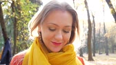 flirten : Pretty female smiles and kiss in forest or park on background of trees with yellow foliage in autumn. Woman in brown sweater with orange scarf in rays of sunlight