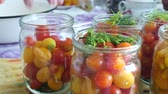 enlatamento : Housewife puts red and yellow cherry tomatoes in glass jar. Homemade juicy spicy marinated vegetable with dill or fennel. Home preservation concept
