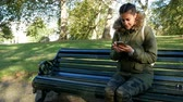 Woman sitting on bench at park and typing text message on smart phone Vídeos
