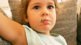 Adorable little caucasian girl sitting on sofa and eating lollipop close up