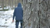 Mysterious man with hood walking on frozen ground in forest motion view