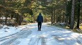 Young man with jacket and hood walking on the middle of frozen mountain road slow motion Vídeos
