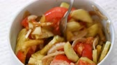 Mixing summer salad with organic tomatoes,peppers and onion seasoned with olive oil and balsamic vinegar