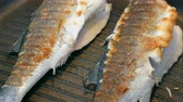 Two whole sea bass fish cooking on hot pan close up Vídeos