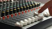 Man moving fader sliders on audio mixer board in music studio close up