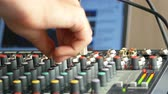 Man adjusting buttons on audio mixer in radio station with computer screen at background