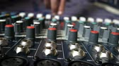 Man adjusting buttons and knobs on audio mixer in music studio indoors close up