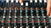 Man hands adjusting fade sliders on audio mixer console in music studio top view Vídeos