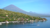 4K Jemeluk Beach and beautiful blue lagoon with Gunung Agung volcano on backgrou