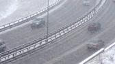 squall : Cars driving on snowy road in winter, traffic on highway in snowfall, blizzard
