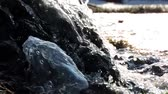Mountain waterfall, creek, river. Water splashes over stones in sunlight