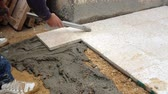 A construction worker fixing tiles of floor with cement