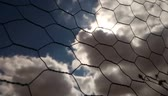 Time lapse of clouds and sun through metal mesh