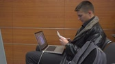 iş kişi : Attractive young man with open laptop, watching the departure time at the airport