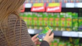 comparação : A young woman is shopping at a store. She is taking a pack of juice from the shelf, viewing, reading the inscriptions on the labels, comparing and choosing. 4K Stock Footage