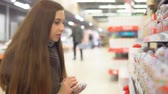 держать : Shop, shopping. Young attractive woman buys chocolate eggs. 4K