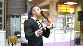 чувство : A young attractive man showing a show in a shopping center. He singing into the microphone Стоковые видеозаписи