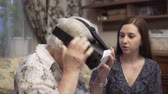 реальность : Granddaughter is showing grandmother virtual reality glasses. An elderly woman for the first time uses virtual reality glasses. 4K Стоковые видеозаписи