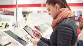 válassza : A young attractive woman is choosing a tablet in a store. 4K