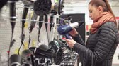 arckifejezés : Young attractive woman is choosing a hairdryer in a store. 4K