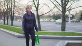 parsel : An attractive middle-aged woman is walking down the street. She is holding a mobile phone and a package. Slow-motion Stok Video