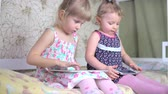 ujj : Little girls play on the tablet and phone. 4k Stock mozgókép