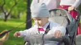 baby carriage : A one-year-old child drives in a stroller with parents in the park. Slow motion