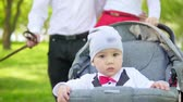 kočár : A one-year-old child drives in a stroller with parents in the park. Slow motion