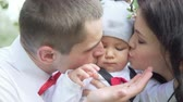 szczęśliwa rodzina : Young happy family. Dad and mom kisses the baby on both sides. Slow motion. Close-up
