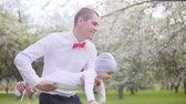 fény : Dad is carrying the baby in the park. Slow motion Stock mozgókép