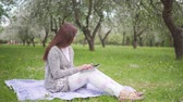 long hairs : Young attractive woman doing internet shopping on a tablet in the park Stock Footage
