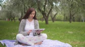 card : Young attractive woman doing internet shopping on a tablet in the park Stock Footage