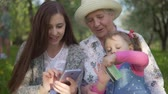 young mother : Young attractive mother grandmother and little daughter doing internet shopping in the park Stock Footage