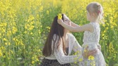 pole : A young mother with a little daughter in a rapeseed field. Slow motion