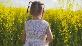 game field : Little girl running in a rapeseed field