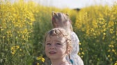 pole : A little girl with her sister looks around in a rapeseed field