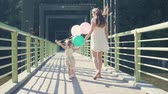 yeşillik : A young woman with a child is walking in the park with balloons