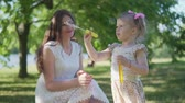 パフ : A little girl with her mom is blowing soap bubbles in the park 動画素材