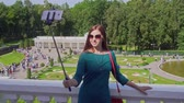 Young attractive woman is photographed on a mobile phone with a stick stick in the park in summer 動画素材