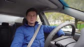 рулевое управление : A man drives a car around the city in the daytime.