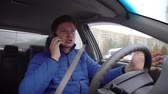 A man is emotionally talking on the phone while driving a car. Стоковые видеозаписи
