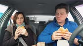 People eat hamburgers in the car