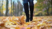 A woman walks through the autumn park.