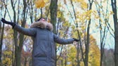 A woman tosses leaves in an autumn park Стоковые видеозаписи
